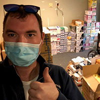 Man giving thumbs up with donations in background